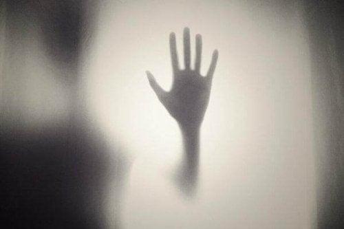 Hand, die an ein Fenster lehnt