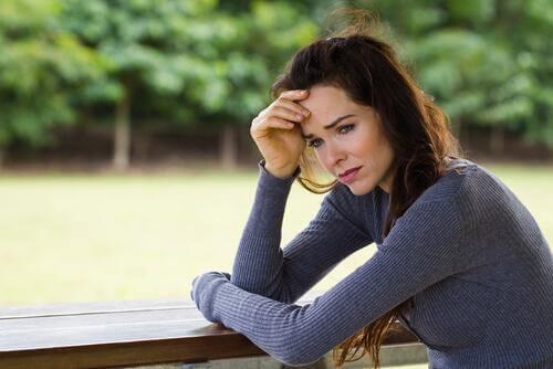 Verzweifelte Frau am Tisch im Park