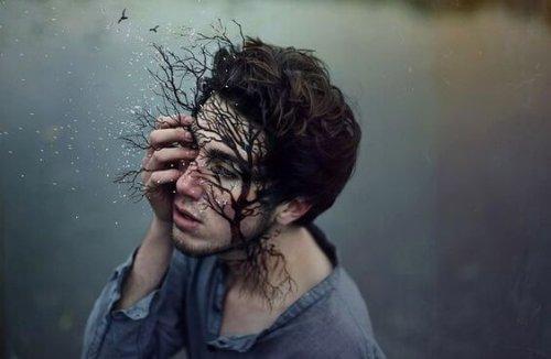 Mann mit Zweigen im Gesicht