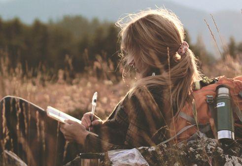 Eine Frau mit Rucksack sitzt auf einem Feld und schreibt in ein Notizbuch