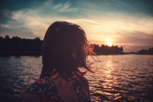 Eine Frau schaut hinaus auf einen See, während die Sonne untergeht