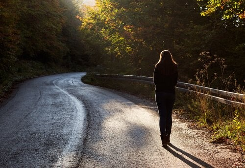 Danke, aber Lebwohl - Eine Frau läuft allein auf einer Straße durch den Wald