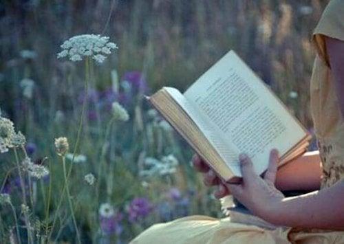 Frau liest ein Buch auf einer Wiese