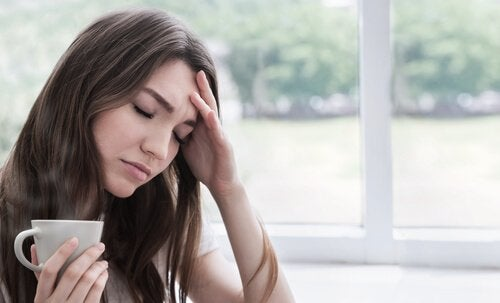 Eine Frau greift sich an den schmerzenden Kopf