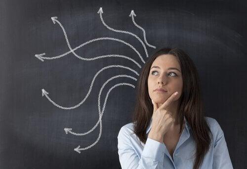 Eine Frau steht vor einer Tafel und denkt nach.