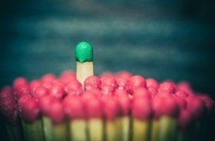 Arten sozialer Macht - Ein grünes Streichholz schaut zwischen vielen roten Streichholzköpfen hervor.