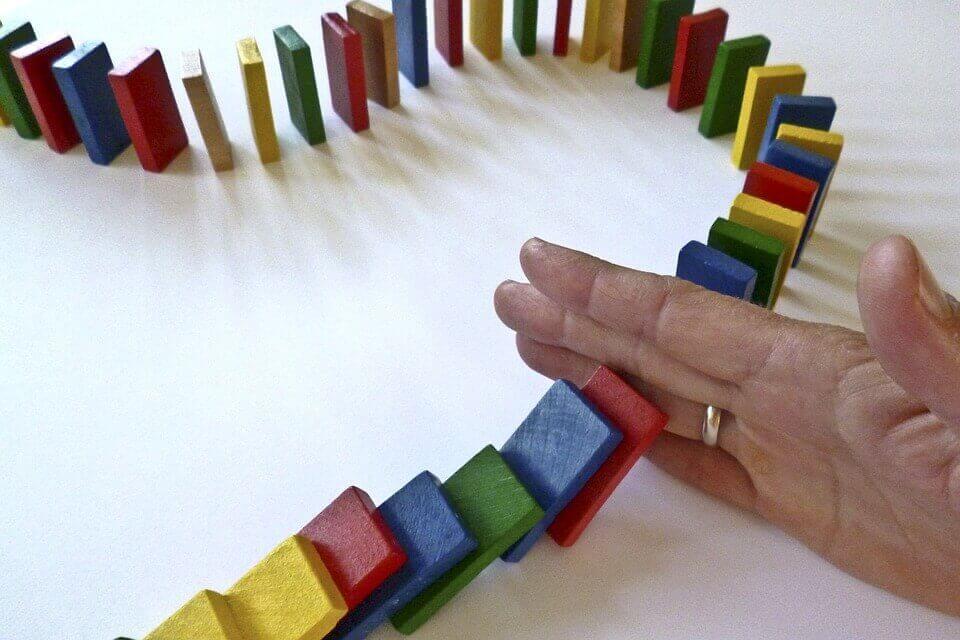 Bunte Dominoschlange wird von einer Hand unterbrochen