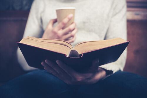 Mann mit Kaffeebecher liest ein Buch