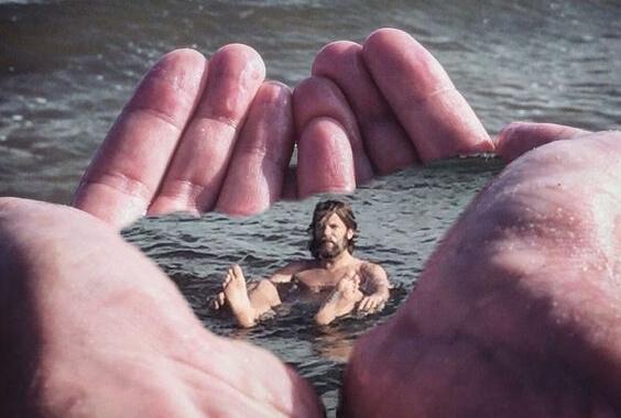 Ein Mann schwimmt in Wasser, welches von zwei großen Händen zurückgehalten wird.
