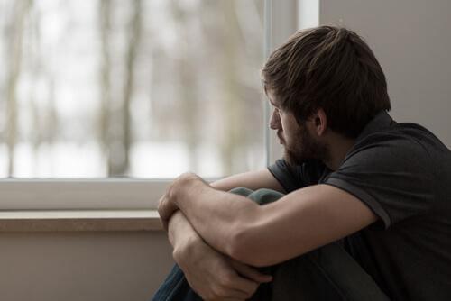 Mann schaut traurig aus einem Fenster