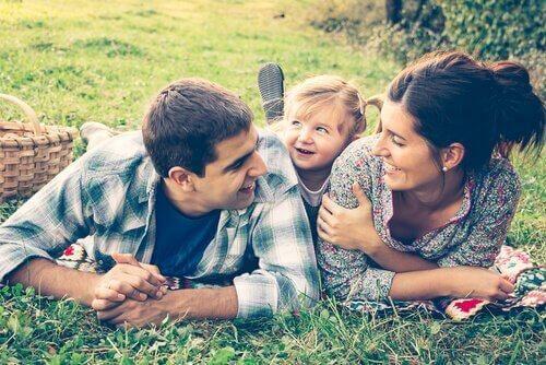 Junge Familie genießt ein Picknick im Grünen.