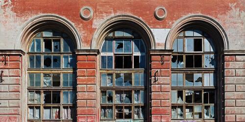 Theorie des zerbrochenen Fensters - Eine rote Hausfassade mit zerbrochenen Fenstern.