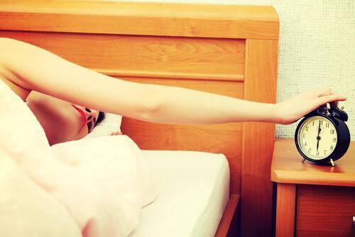 Müde Frau streckt den Arm aus dem Bett, um den Wecker auszuschalten.