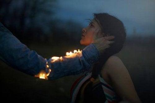 Arm, der Feuer gefangen hat, liebkost Gesicht einer Frau