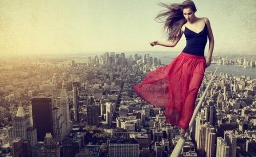 Frau balanciert hoch über einer Stadt