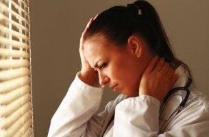 Mitgefühlserschöpfung - Erschöpfte Frau fasst sich an den Kopf