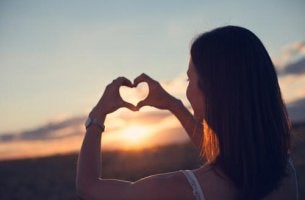 Sich um sich selbst kümmern - Frau formt Herz mit ihren Händen