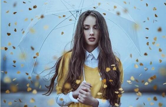 Auf Gefühle hören - Blätter in Herzform regnen auf eine junge Frau herab.