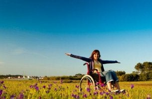 Funktionsvielfalt - Eine glückliche Frau im Rollstuhl steht auf einer Blumenwiese.