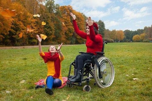 Eine junge Frau im Rollstuhl und eine Freundin amüsieren sich bei einem Ausflug ins Grüne.