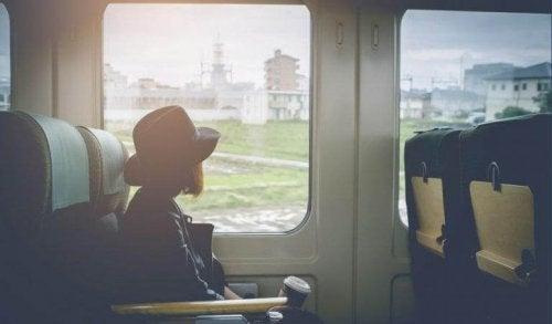Frau sitzt im Zug und starrt aus dem Fenster