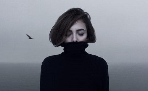 Frau trägt schwarzen Rollkragenpullover über dem Mund