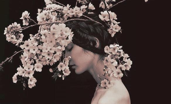 Frau mit geschlossenen Augen unter blühenden Zweigen
