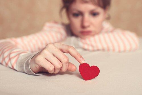 Nachdenkliche Frau berührt rotes Herz