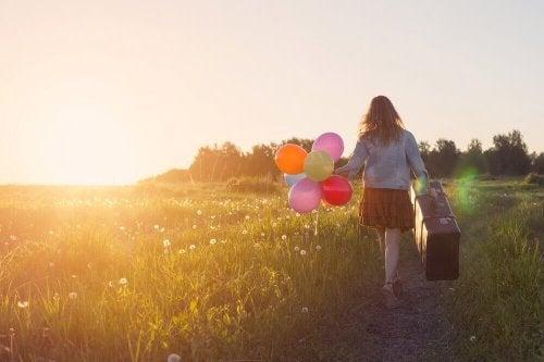 Frau mit Koffer und Ballons in ihren Händen