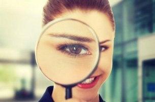 Neugier und Intelligenz - Lächelnde Frau schaut durch eine Lupe.