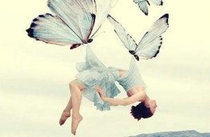 Emotionale Wunden heilen - Frau wird von Schmetterlingen getragen