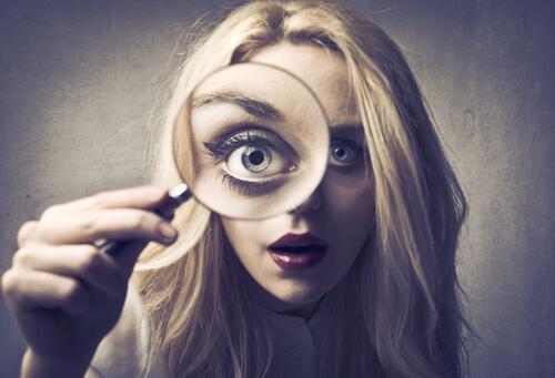 Eine blonde Frau schaut mit dem rechten Auge durch eine Lupe.