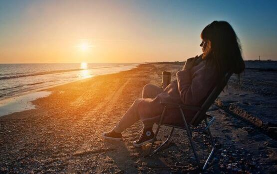 Frau sitzt auf einem Stuhl am Strand