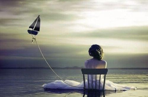 Mauer der Einsamkeit - Frau sitzt einsam auf einem Stuhl im Meer