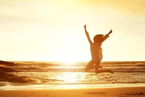 Der Routine entkommen: Frau springt am Strand in die Luft