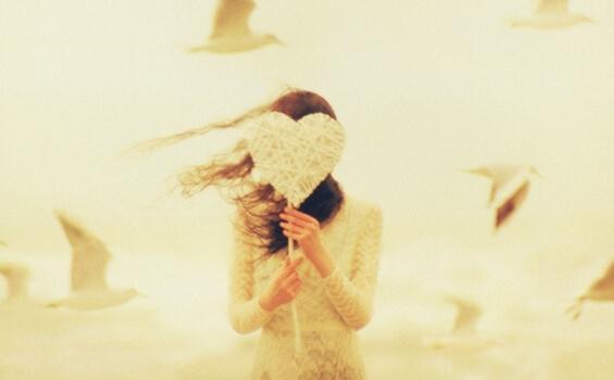 Eine Frau hält sich ein gebasteltes Herz vor's Gesicht.