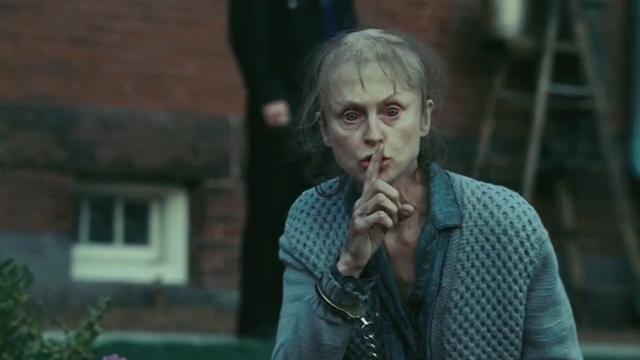Frau hält sich ihren Finger vor den Mund, um etwas zu verheimlichen