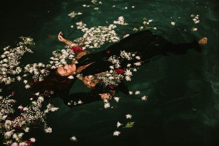 Frau treibt im Wasser zwischen Blumen