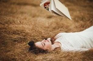 Ein Mädchen liegt im Stroh und liest ein Buch, das über ihr schwebt. Sie hat keine Angst vor Freizeit.