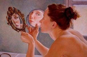 Narzissmus und Selbstwertgefühl - Frau betrachtet sich in zwei Spiegeln, die symbolisch für Narzissmus und Selbstwertgefühl stehen