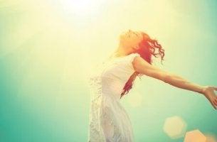 Selbstmotivation - Glückliche Frau springt in der Sonne.
