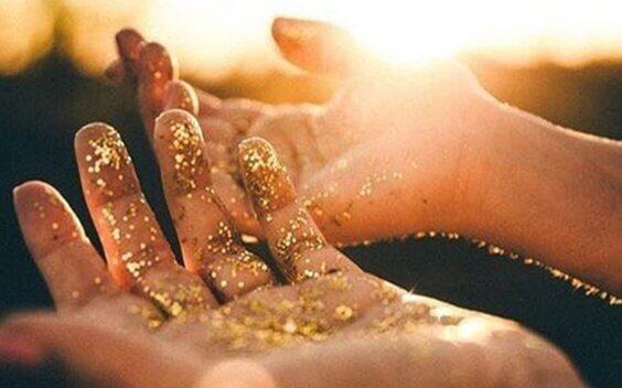 Hände mit goldenem Puder