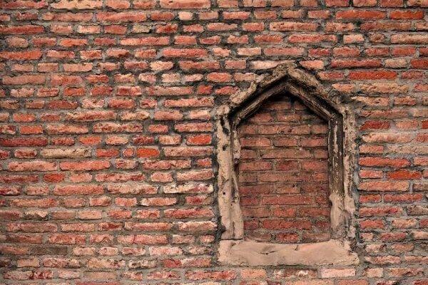Eine Hauswand mit einem zugemauerten Fenster.