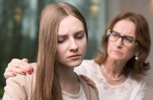 Jugendliches Selbstwertgefühl - Mutter legt ihrer traurigen Tochter tröstend die Hände auf die Schultern.