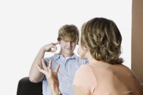 Jugendlicher hält sich die Ohren zu, als seine Mutter zu ihm spricht