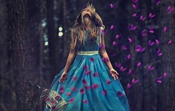 Eine blonde Frau ist allein im Wald und von zahlreichen, lilafarbenen Schmetterlingen umgeben.