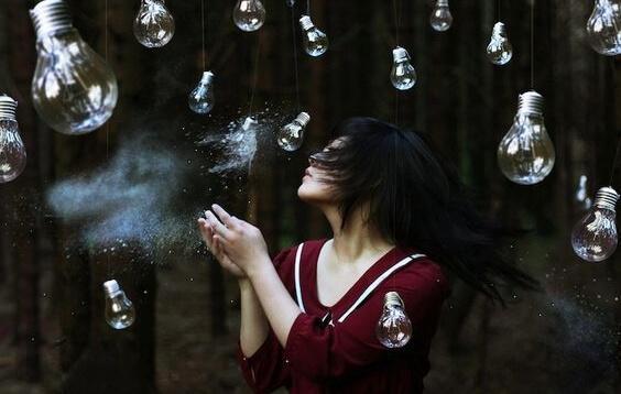 Über einer jungen Frau hängen lauter Glühbirnen.