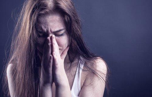 Eine verzweifelte junge Frau hält sich die Hände vors Gesicht.