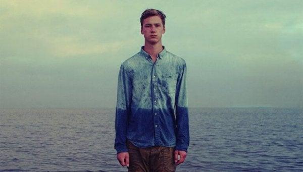 Junger Mann vor dem Meer, das Wasser steht ihm bis zum Bauch