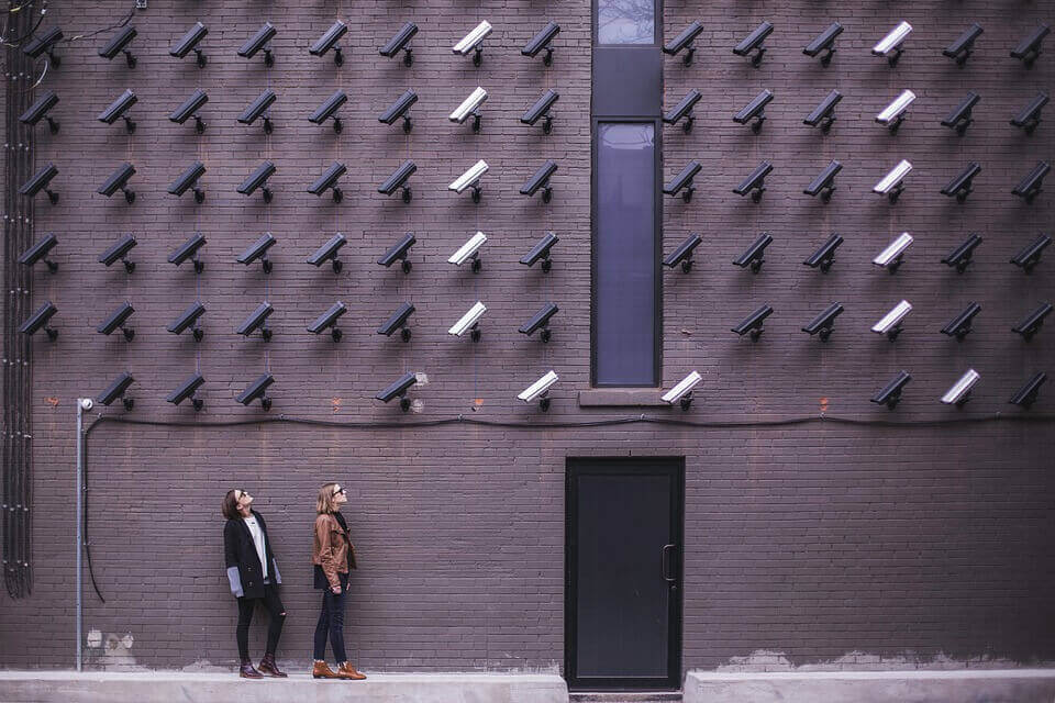 Viele Kameras an einer Hauswand zeigen auf zwei Mädchen.